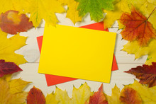 Frame Autumn Leaves With Yello Envelope On Wooden Background. Colorful Template For Design