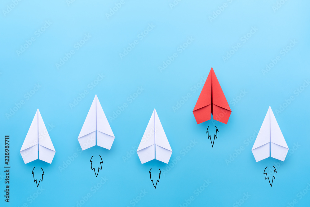 Fototapeta Red paper plane leading among a white planes on blue background. Business competition and Leadership concept