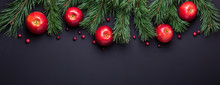 Christmas Background With Tree Branches, Red Apples And Cranberries. Dark Wooden Table. Banner. Top View. Copy Space