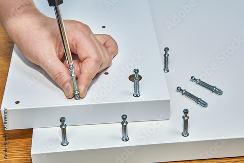 Fotografie, Tablou Carpenter is screwing screw-bolt for furniture cam lock.