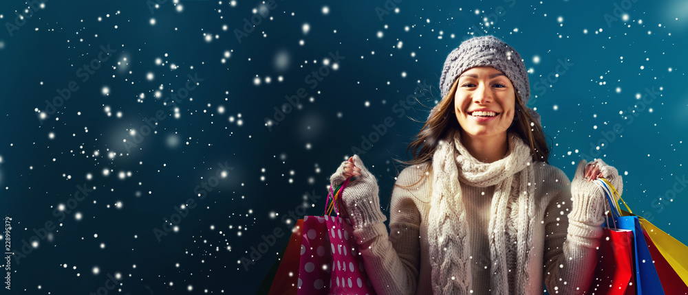 Fototapeta Happy young woman holding shopping bags in a snowy night