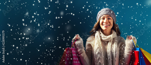 Cuadros en Lienzo Happy young woman holding shopping bags in a snowy night