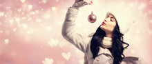 Woman Holding Christmas Bauble On Shiny Hearts Background