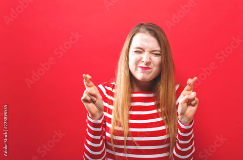 Photographie  Young woman crossing her fingers and wishing for good luck