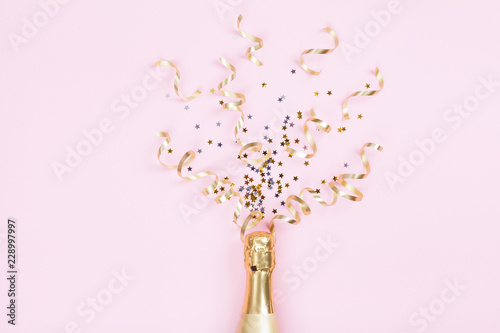 Champagne bottle with confetti stars and party streamers on pink background. Christmas, birthday or wedding concept. Flat lay style.
