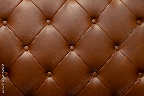 Poster Macarons Brown genuine leather sofa background.