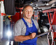 Skilled mature male mechanic taking notes in notebook about car repair at auto service