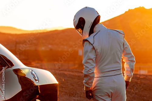 Ingelijste posters F1 A Helmet Wearing Race Car Driver In The Early Morning Sun Looking At His Car Before Starting