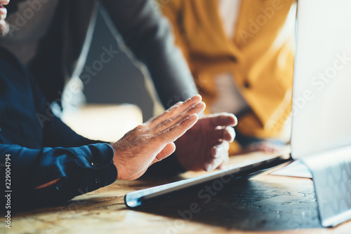 Fototapety, obrazy: Startup and millenial business concept. Close-up of man's hands working with laptop and explaining project to another manager