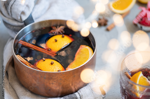 Photo Mulled wine hot drink with oranges and spices in copper pot