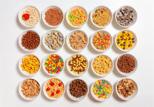 Set Of Different Cereals On A White Background. 20 Bowls With Cornflakes, Kasha, Cereals And Berries. The Concept Of Breakfast Food. Flat Lay, Top View