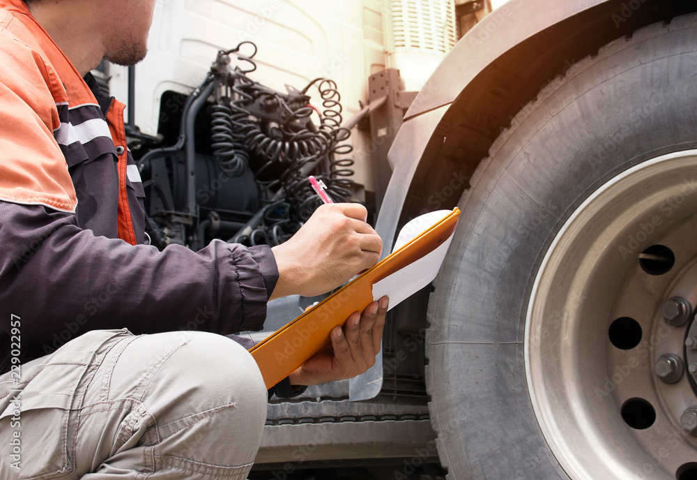 Fotografie, Obraz  Inspection safety a trucks, truck driver holding clipboard with checking a truck tire
