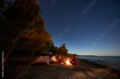Fototapeta Night camping on sea shore. Happy young man and woman hikers relaxing in front of tent at campfire under evening sky on clear blue water and green forest background. Active lifestyle concept. obraz na płótnie