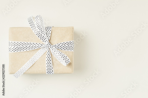 Fotografía  Wrapped gift box with ribbon bow on a white background, copy space