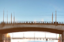 Blurred Reflection Of A Bridge On Surface Of A Polluted Urban River. Drainage Planned In The Riverbed