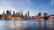 4k cinemagraph of New York City Manhattan, financial district night skyline, cityscape at Brooklyn bridge park during sunset, dusk, twilight, blue hour, skyscrapers, moving clouds, light streaks