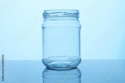 Empty glass jar. Reflective surface, blue lighting.