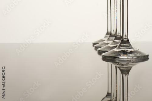 Glass cups stems. Reflective surface. White background and free space for text.