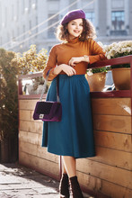 Outdoor Full Body Fashion Portrait Of Young Beautiful Happy Smiling Woman Wearing Stylish  Beret, Orange Turtleneck, Midi Green Blue Skirt, Ankle Boots, Holding Quilted Purple Bag, Posing In Street