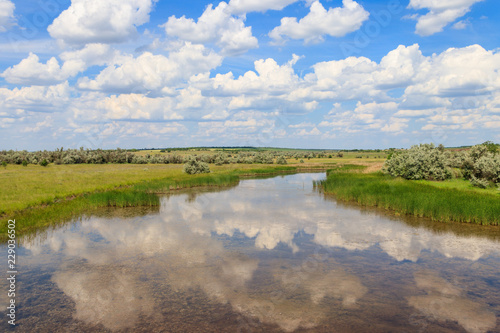 Summer landscape with small river and blue cloudy sky