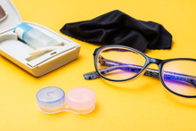 Accessories For Storing Lenses: Container, A Bottle Of Liquid And Tweezers In A Case, Glasses And Cloth On A Yellow Background. Concept - Glasses Against Lenses