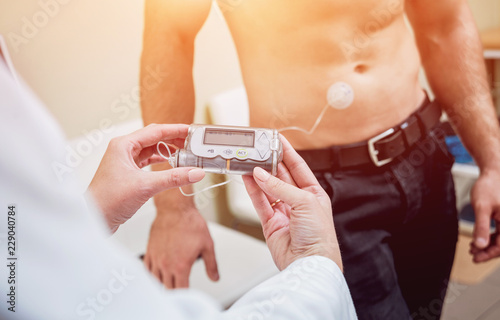 Fotografía  Doctor with an insulin pump connected in patient abdomen and holding the insulin pump at his hands