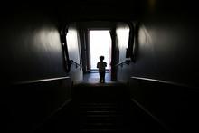 Silhouette Of A Little Boy Walking Down A Dark Staircase