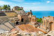 canvas print picture - Ruins of the Ancient Greek Theater in Taormina on a sunny summer day with the mediterranean sea. Province of Messina, Sicily, southern Italy.