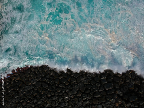 Tuinposter Poort Aerial top view of sea waves hitting a stones from a jetty in pier. Drone view
