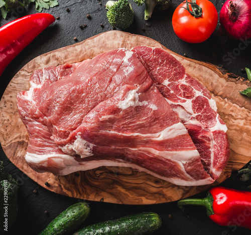 In de dag Vlees Raw meat, beef steak on cutting board on black background with ingredients for cooking. Top view