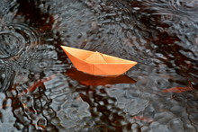 Origami Orange Paper Boat Floats On The Water Under The Rain Drops