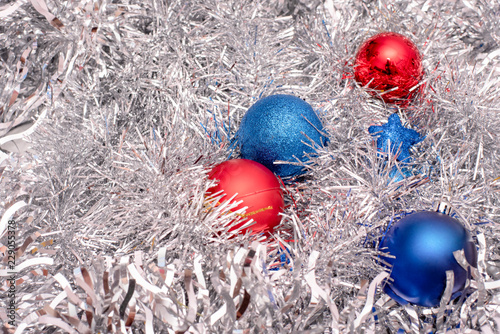 Obraz Beautiful Christmas toys of blue and red colors on tinsel - fototapety do salonu