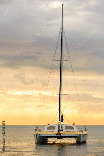 Catamaran glides at twilight on water surface of the baltic sea Fototapeta