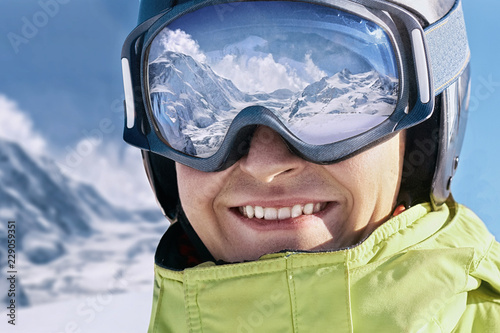 Portrait of man at the ski resort on the background of mountains and blue sky.A mountain range reflected in the ski mask