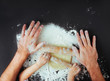 canvas print picture - Top view of fathers and kids hands rolling the dough on black background