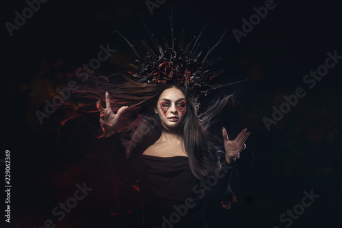 Ingelijste posters Halloween Terrible horror Halloween Vampire Woman portrait. Beauty Vampire Witch lady with blood on mouth posing in deep forest. Fashion Art design. holds a candle in his hands and reads curses