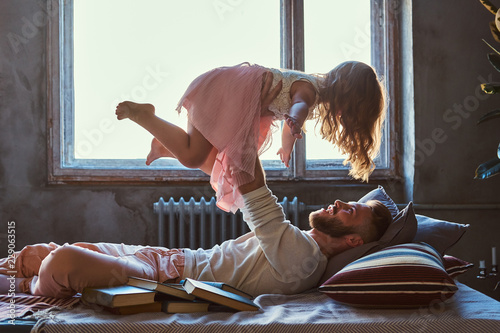 Poster Ecole de Yoga Dad and daughter in bed. Father playing with adorable daughter in bedroom.