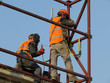 Welder working on the construction site against the clear blue sky. Construction workers on scaffolding, welding work