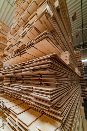 Fototapeta warehouse shelves are filled with floorboard for sales of production. Wood processing plant. Close-up obraz na płótnie