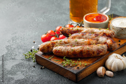 Fotografia Fried sausages with sauces and herbs on a wooden serving Board