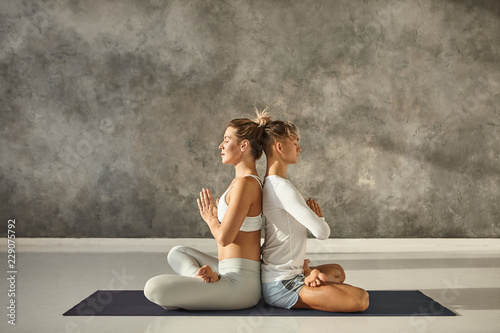 Horizontal side view of attractive young couple practicing yoga together indoors. Peaceful Caucasian man and woman sitting back to back in lotus pose, holding hands in namaste, keeping eyes closed