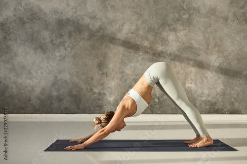 Full length side view of beautiful young fit woman in sportswear working out ind Fototapeta