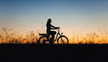 Silhouette Of A Girl On The E-bike Or Electric Bicycle On The Sunset Background. Country Style. Transportation In The Village. Copy Space. Female. Travel.