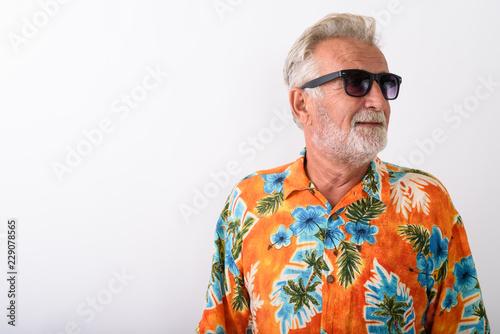 Studio shot of happy senior bearded tourist man smiling while th