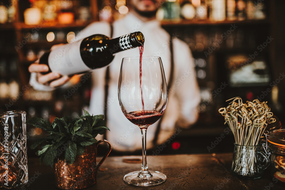 Fototapety, obrazy: Close up shot of a bartender pouring red wine into a glass. Hospitality, beverage and wine concept.