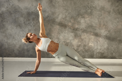 Fototapeta Pretty girl wearing leggings and short top standing in side plank on one hand at gym, training body core and balance, strengthening abs muscles. Attractive female doing planking bodyweight exercise obraz