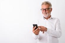 Studio Shot Of Happy Senior Bearded Man Smiling While Using Mobi