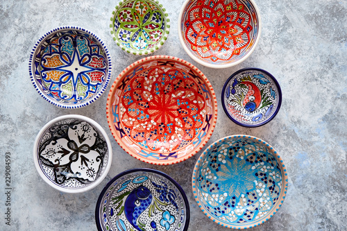 Garden Poster Ready meals Collection of empty moroccan colorful decorative ceramic bowls. Composition captured from top view, flat lay. Placed on grey stone background.