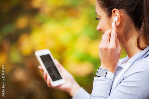 Photo Photo of Joyful Fitness Woman 30s in Sportswear Touching Bluetooth Earpod and Ho