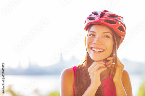 Cyclist woman putting bike helmet on - head protection on outdoor sport activiy or commute lifestyle in city. Asian girl on bicycle during summer.